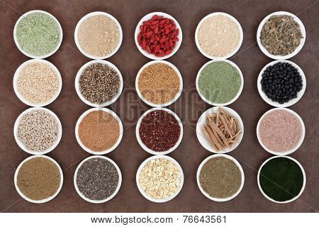 Health food and body building powders in porcelain dishes over natural lokta paper background.