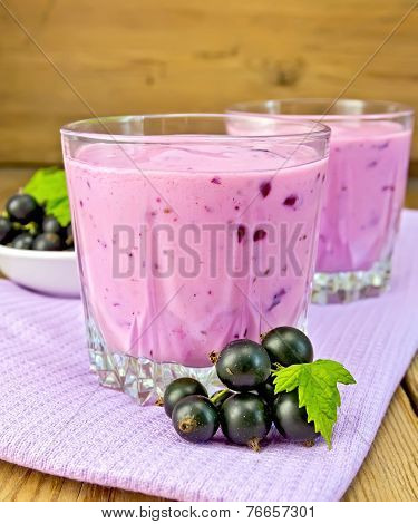 Milkshake with blackcurrants on napkin and board