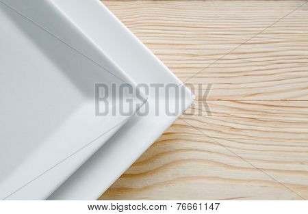Square White Plates Over Wooden Table