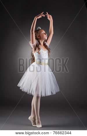 Sweet little ballerina posing on gray backdrop