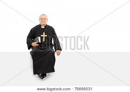 Mature priest sitting on a blank panel isolated on white background