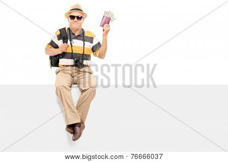 Mature tourist holding passport with money seated on a panel isolated on white background