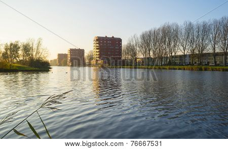 Highrise along a river at sunset in autumn