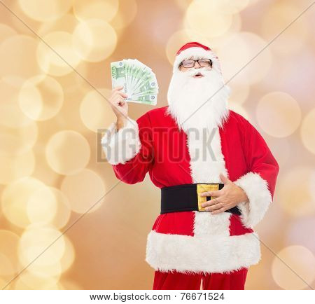 christmas, holidays, winning, currency and people concept - man in costume of santa claus with euro money over beige lights background