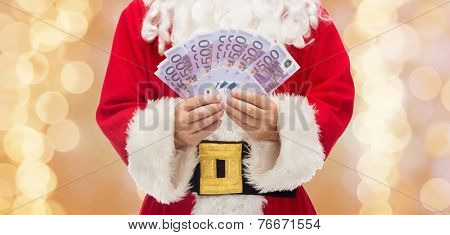 christmas, holidays, winning, currency and people concept - close up of santa claus with euro money over beige lights background