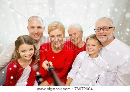 family, holidays, generation, christmas and people concept - smiling family with camera and selfie stick taking picture at home