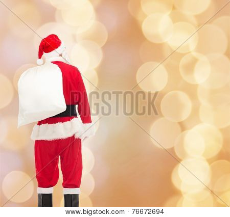 christmas, holidays and people concept - man in costume of santa claus with bag from back over beige lights background