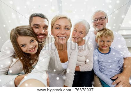 family, technology, generation and people concept - happy family sitting on couch and taking self portrait with camera or smartphone at home