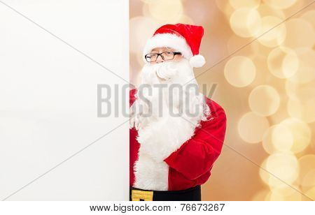 christmas, holidays, advertisement and people concept - man in costume of santa claus with white blank billboard making hush gesture over beige lights background