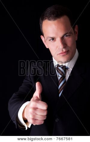Businessman Giving Consent, With Thumb Up, Isolated On Black Background. Studio Shot.