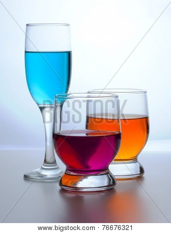 three glasses with drinks different colored glasses
