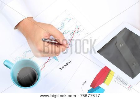 Young Businessman Working In The Office,  Sitting At His Desk, Analyzing  Data In  Graphics, Hot Cof