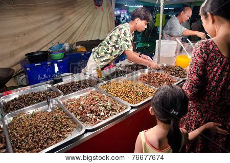 An unidentified man selling fried insects in Bangkok, Thailand