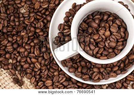 Roasted brown Coffee Beans in and around a cup