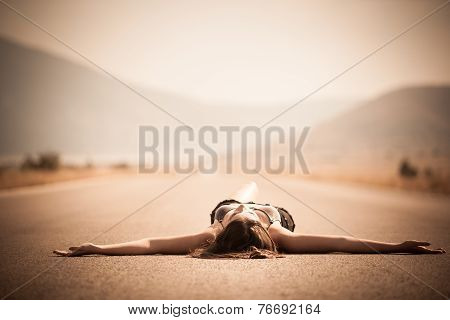 Woman lying on the highway road enjoying sun and summer in the middle of nowhere