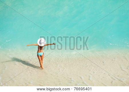 Top view of woman with white hat standing in ocean