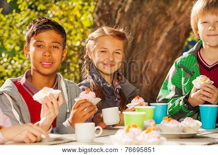 International kids drink tea with cupcakes