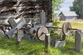 stock photo of scythe  - Grindstones this side a wooden buildings - JPG