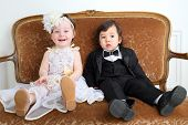 image of little black dress  - Laughing little girl in beautiful white dress and serious boy in black suit sitting on couch - JPG