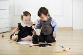 stock photo of lurex  - Two young children sitting on floor and draw colored markers - JPG