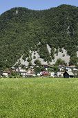stock photo of avalanche  - Village below the hill in Slovenia there is a change of an avalanche - JPG