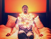 foto of sad christmas  - a man draped in christmas lights sitting on a bed looking depressed toned with a vintage filter - JPG