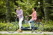 stock photo of tandem bicycle  - Young couple riding on the bicycle in the park - JPG