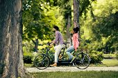 foto of tandem bicycle  - Young couple riding on the bicycle in the park - JPG