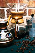 Vintage coffee filter with a wooden holder over a glass jug for brewing fresh coffee alongside a patterned decorative cezve for making Turkish coffee and a metal percolator poster