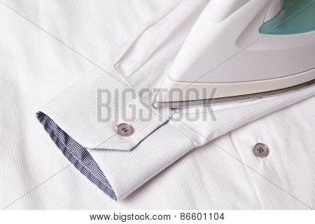 Close Up Of Iron Ironing Sleeve Of Cotton Shirt