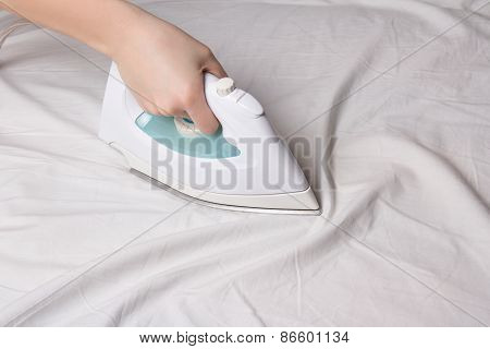 Iron In Female Hand Ironing Cotton Linen