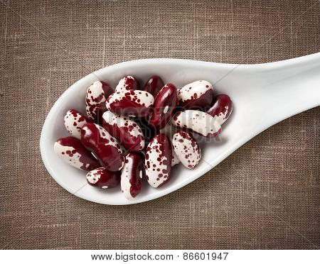 Speckled Beans In White Porcelain Spoon / High-res Photo Of Grain In White Porcelain Spoon On Burlap