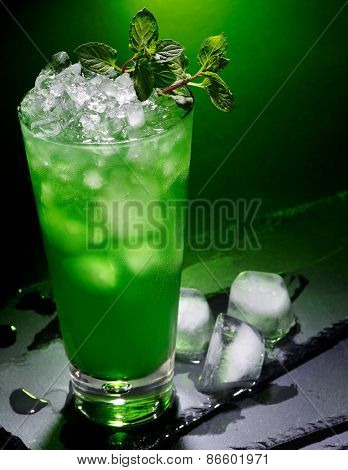 Green drink  with cube ice and mint leaf on dark background.17