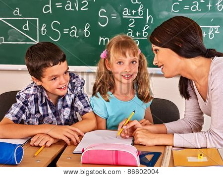 Group of school child with young teacher sitting on desk in classroom.