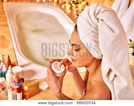 Woman applying moisturizer at bathroom. Towel on head.