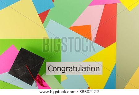 Graduation Cap And Word On Colorful Paper Background