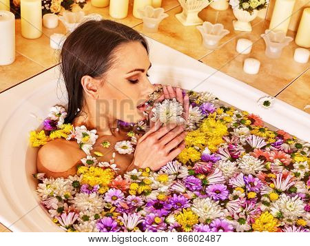 Woman relaxing at water spa. A lot of flower.