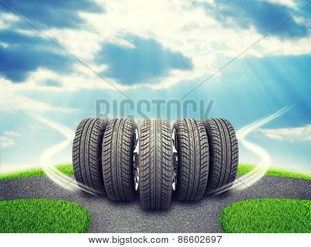 Wedge of new car wheels on road fork  and green grass field