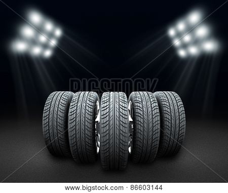 Wedge of new car wheels. Dark background with spotlight