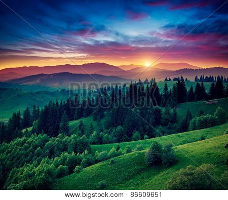 Green hills glowing by warm sunlight at twilight. Dramatic scene. Colorful sky, red clouds. Carpathian, Ukraine, Europe. Beauty world.