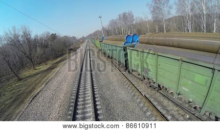 Aerial view of Long freight transports big metal pipes in green carriages.