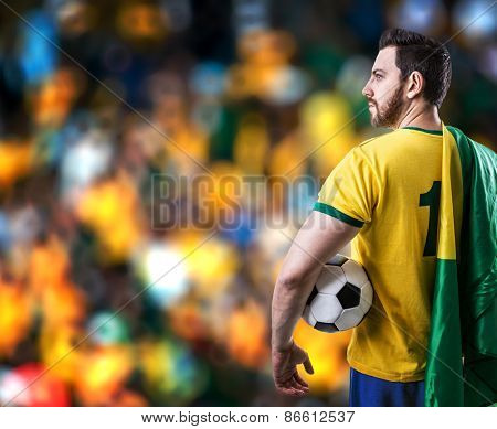 Brazilian soccer player holding the flag of Brazil and a ball in the stadium