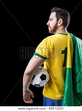 Brazilian soccer player holding the flag of Brazil and a ball on black background
