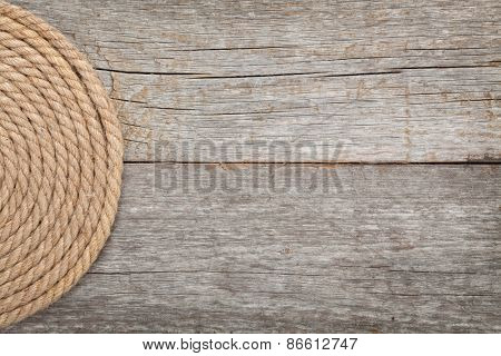 Roll of ship rope on wooden texture background