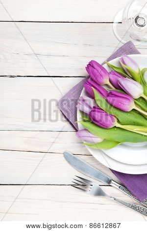 Purple tulip bouquet over plate on wooden table. Top view
