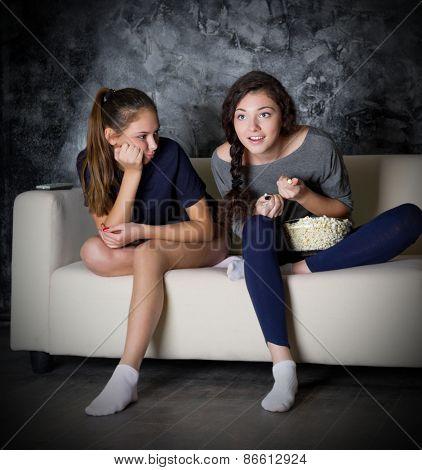Two girls looks TV at dark room