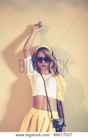 Beautiful Retro Woman Posing In Front Of A Yellow Wall And Holding An Old Camera