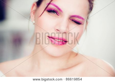 The Woman With A Bright Pink Make-up Winks.