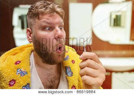 Strange adult man looks at the hair from his nose in home interior