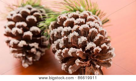 Two fir cones on a wooden table